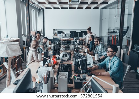 Business routine. Group of young business people concentrating at their work while sitting at the large office desk together #572801554