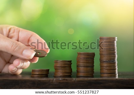 Business saving concept.Woman hand holding antique coin putting on coin stack ,investment concept.