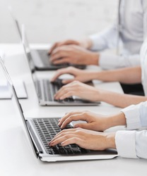 business, school and education concept - group of people working with laptops in office