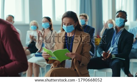 Business seminar. Quarantine. Attentive multi-ethnic corporate men and women with masks listening to business lecture presentation in conference meeting room. Social distancing.