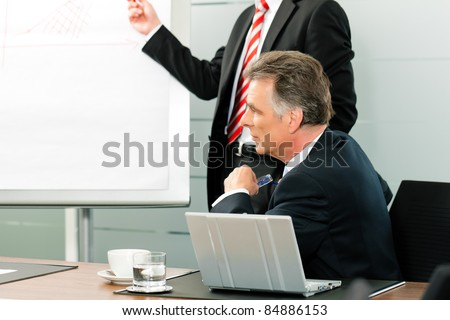 Business - Senior Manager or boss in meeting while a colleague is presenting a new strategy - stock photo