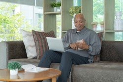 Business senior old elderly Black American man, African person using a smartphone or mobile phone in living room at home in technology device concept. Lifestyle people.