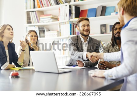 Business shaking hand with a client in office