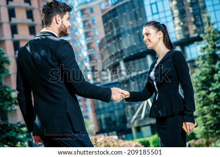 Business shaking hands. Confident and successful businessmen shaking hands and smiling looking at the camera. Business woman holding a man\'s hand.