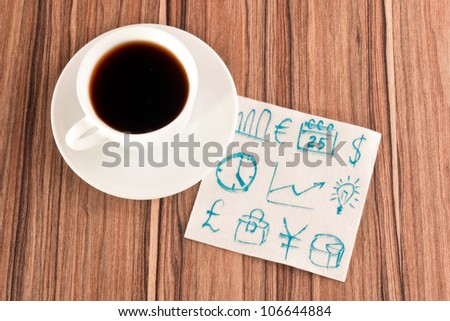 Business signs on a napkin and cup of coffee