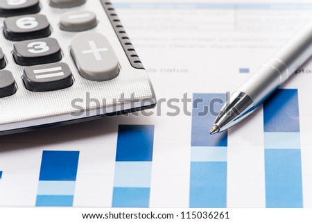 Business silver pen and calculator over office charts close-up