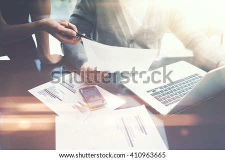 Business situation.Meeting of financial analysts.Photo female showing document.Man holding report, using laptop.Working process modern office,discussion startup. Horizontal. Film and bokeh effects