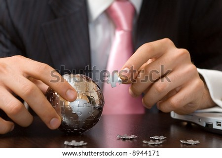 business solution concept with businessman playing a globe puzzle