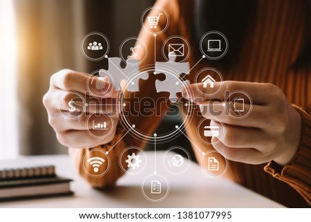 Business solutions and success concept. Businessman hand connecting jigsaw puzzle at office with VR icon in morning light