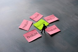 Business solutions, problem solving and brainstorming concept. Miniature man looking at red paper with text PROBLEM and green paper with text SOLUTION.