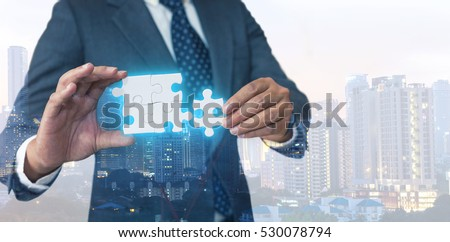 Business solutions, success and strategy concept. Businessman hand connecting jigsaw puzzle. Double exposure and background down opacity.