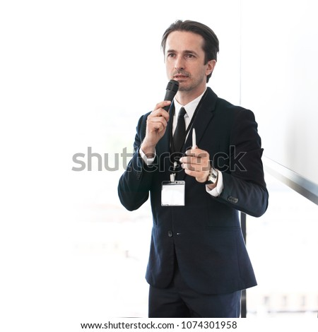 Business speaker giving a presentation to audience #1074301958