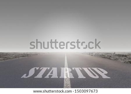Business Startup Concept : Startup message or words print on asphalt roadway leading toward to destination.