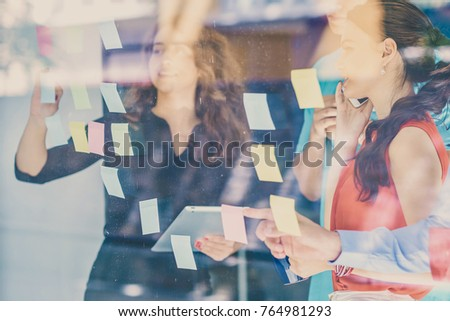 business, startup, planning, management and people concept - happy creative team writing on stickers at office glass board #764981293