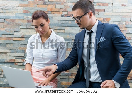 Business startup presentation on laptop computer in modern office done by preety young businesswoman and businessman