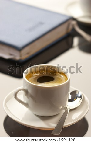 business still life: cup of coffee with writing-pad on the desk