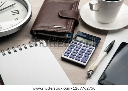 business still life from a notepad, a smartphone, a clock, a cup of coffee, a calculator  #1289762758