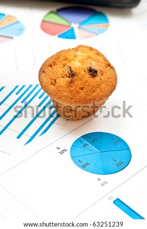 Business still-life with diagrams, charts, numbers and cake