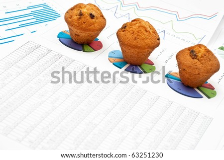 Business still-life with diagrams, charts, numbers and cakes