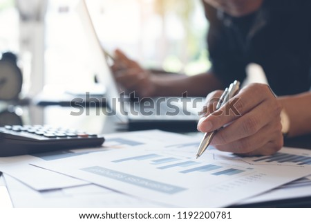 Business strategy analysis. Businessman, accountant holding pen working on laptop computer, accounting financial business report and accountancy document with calculator on desk at office, close up