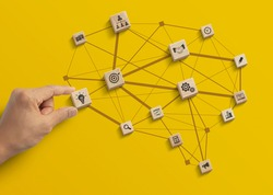 Business strategy, business management or business success concept. Hand is arranging wooden blocks with business icon in low polygon brain shape network on yellow background.