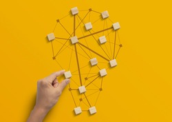 Business strategy, business management or business success concept. Hand is arranging wooden blocks in low polygon light bulb shape network on yellow background.