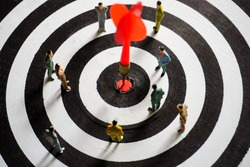 Business strategy conceptual photo. Group of businessman miniature figures standing and meeting on dartboard with red dart arrow hitting in the target center.