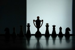Business strategy conceptual photo – Silhouette of trophy stand in office table with chess pawn
