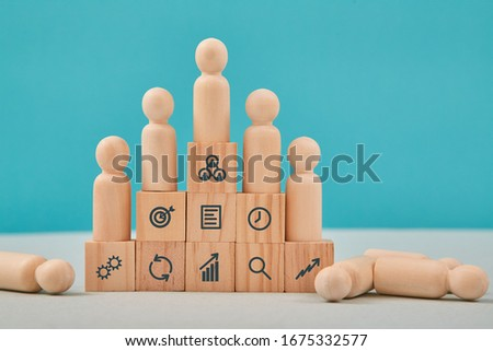 Business strategy. Growth and development. Pyramid of wooden cubes with people miniatures on steps and management signs