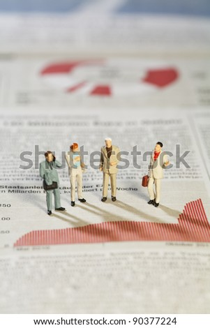 Business Strategy Meeting, four miniature models of businessmen standing above a bar graph as though in a meeting.