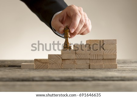 Business success and promotion concept with a businessman moving the queen piece up a series of steps formed by building blocks. #691646635