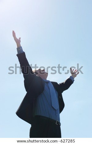Business success as the man raises his arms in the air