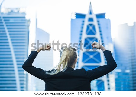 Business success! Celebrating strong confident businesswoman flexing against a city high-rise view.