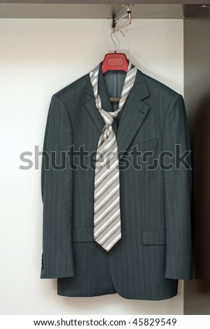 Business suit hanging on the rack in the wardrobe