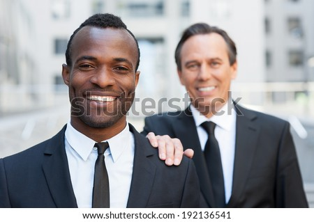 Business support. Confident senior man in formal wear holding hand on shoulder of young African man that looking at camera and smiling