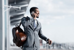 Business Talk. African Man Talking on Phone at Airport and Waiting Taxi