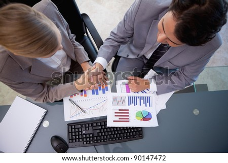Business team agreeing on a deal in a meeting room