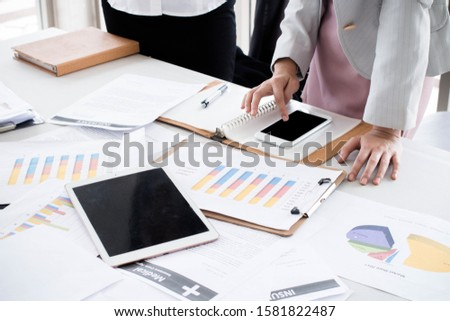 Business team analyzing income charts and making a decisions on desk office with document paper report. Marketing and exploring market data for organization. Business analysis and strategy concept.
