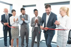 Business team applauds on cutting of red ribbon and grand opening