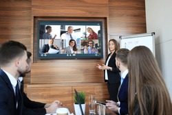 Business team at office, businessman presenting and discussing successful financial report of their company, on screen of plasma TV at meeting room, talking to his colleagues in video conference.