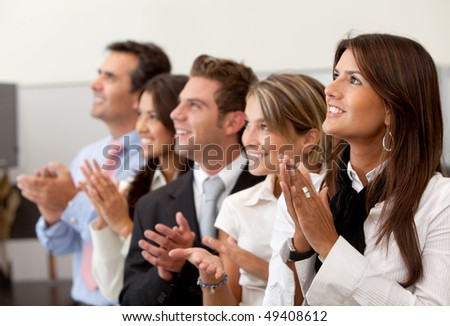 Business team at the office applauding and smiling