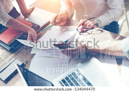 Business team brainstorming in office. Marketing plan researching. Paperwork on the table, laptop and mobile phone. Statistic graph overlay, icon innovation interface