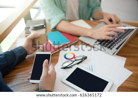 business team  briefing marketing strategy with smart phone, tablet, notebook, and laptop on wooden desk with,Freelance work at home office. Writing note on a book. #626365172