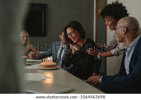 Business team celebrating female colleague's birthday with cake in office. Birthday celebration of a female associate during a staff meeting.