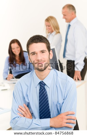 Business team close-up of handsome businessman with attractive happy colleagues