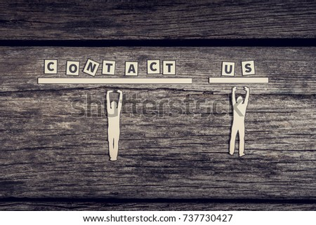 Business team Contact Us concept with cut outs of two paper men supporting the text from below over a rustic wood background with copy space. #737730427