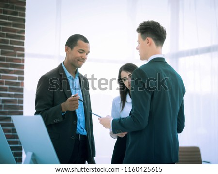 business team discussing business issues standing in the office #1160425615