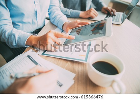 Business team discussing report on digital tablet #615366476