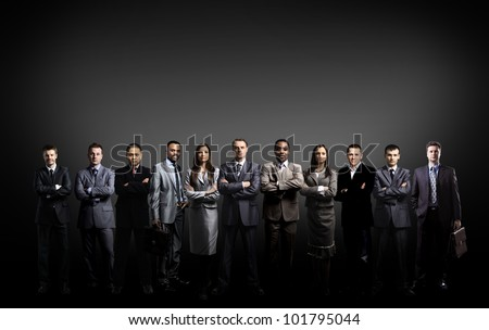 business team formed of young businessmen standing over a dark background - stock photo