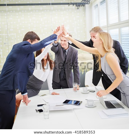 Business team giving each other a high five as motivation in conference room